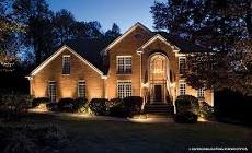 Wide shot of home front lit up at night. Moore's Landscape Lighting. Omaha