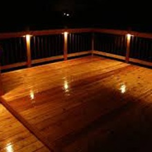 A home deck with decorative lightiing at night. Moore's Landscape Lighting Omaha