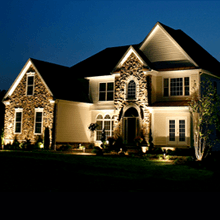 Front of two story home lit up at night. Moore's Landscape Lighting services in Omaha.