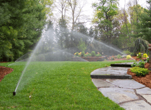 wide shot of a lawn irrigation system showing watering of the lawn.