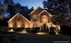 Front of brick house lit up at night. Moore's Landscape Lighting service s in Omaha.