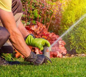 close of man (hands only) adjusting a lawn sprinkler.