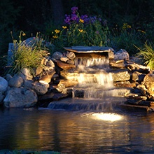 Water feature with landscape lighting. Moore's Irrigation and Landscape Lighting services in Omaha.