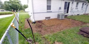 Back of home with yard being sodded after re-slopping for property drainage.