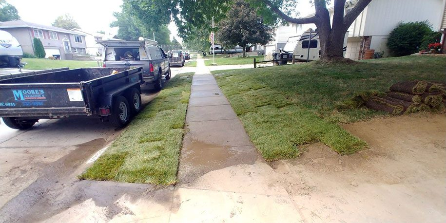 Lawn being re-sloped for property drainage with sod.