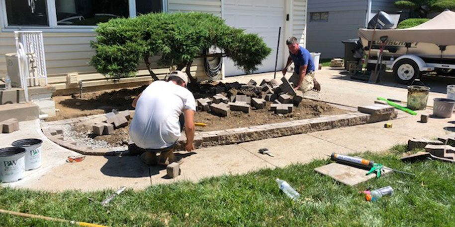 two men performing landscaping after property draining solution has been added to a home.
