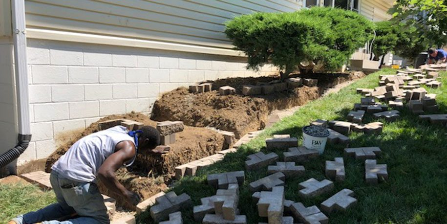 man installing a retaining wall for property drainage.